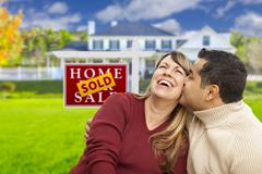 Happy Mixed Race Couple in Front of Sold Real Estate Sign. Piirros