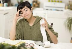Multi-ethnic Young Woman Agonizing Over Financial Calculations in Her Kitchen Stock Photos