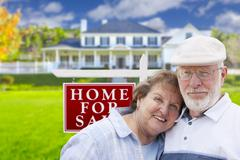 Happy Senior Couple Front of For Sale Real Estate Sign and House. - stock illustration