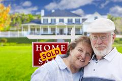 Senior Couple in Front of Sold Real Estate Sign and House - stock illustration
