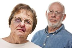 Battered and Scared Woman with Ominous Angry Man Behind. - stock photo