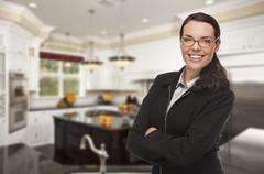 Attractive Mixed Race Young Woman Standing in Beautiful Custom Kitchen. - stock photo