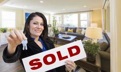 Happy Hispanic Woman with House Keys and Sold Sign in Beautiful Living Room. - stock illustration