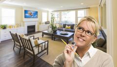 Attractive Daydreaming Woman with Pencil Inside Beautiful Living Room. Stock Photos