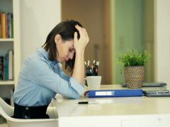 Sad, overwhelmed businesswoman working with documents sitting by table NTSC - stock footage