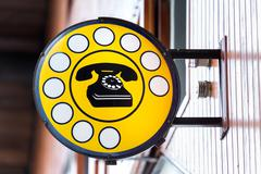 Public telephone indicated in the cartel Stock Photos