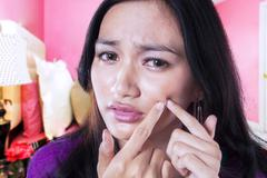 Young girl squeeze her acne Stock Photos