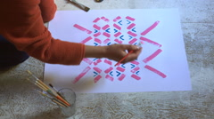 Close Up of Young Woman Painting Pattern With Pink Paint on White Sheet Stock Footage