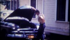 2013 - young man checks under the hood on his car - vintage film home movie Stock Footage
