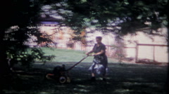 2016 - grandma cuts the grass in the backyard - vintage film home movie Stock Footage