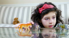 Close up of a cute girl playing with animal toys on a table, dolly Stock Footage