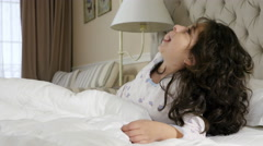 A cute girl in a nightgown chatting on a mobile / cell phone lying on a bed Stock Footage