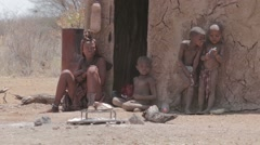 Himba woman with childs on the neck in the village Stock Footage