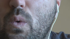 Close up white man face with beard listening music at headphones, whistle, mouth - stock footage