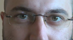 Extreme close up white young man wearing eyeglasses smiling happy to the camera Stock Footage