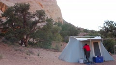 Man enters camping tent in the desert Stock Footage