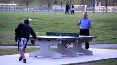 People playing table tennis and make a phone call at park Stock Footage