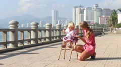 blonde girl in sits on chair and mother claps - stock footage