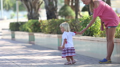 Blonde girl in Ukrainian blouse leads mother away by hand Stock Footage