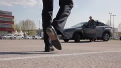 Businessman walking towards a big car and a car seller Stock Footage