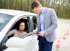 Driving instructor and woman student in examination area Stock Photos