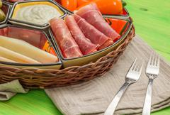 Basket with several Spanish tapas on green table - stock photo
