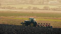 Tractor Plows Field With Birds Swarming Around Stock Footage