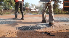 Worker throwing pebble at the road's construction site. Stock Footage