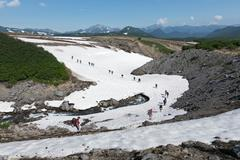 Stock Photo of Group of tourists traverse mountain river on snowfield. Far East, Russia