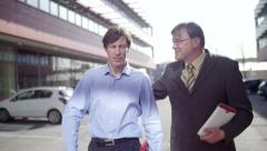 Slow motion of two business men walk and talk friendly - stock footage