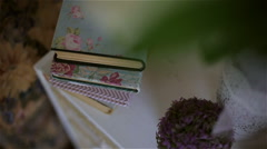 Bouquet of lilac flowers in a pot and old books Stock Footage