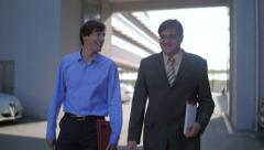 Slow motion of two business men walk and talk friendly Stock Footage