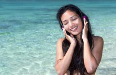 Dreamy woman listening to headphones on a background of the sea Stock Photos