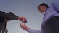 Men exchanging keys and shaking hands Stock Footage
