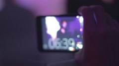 Person filming DJ performance at night club, smartphone in hand Stock Footage