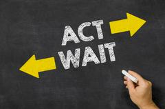 Act or Wait written on a blackboard Stock Photos