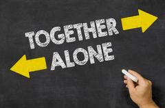 Together or Alone written on a blackboard Stock Photos