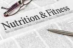 A newspaper with the headline Nutrition and Ftitness - stock photo