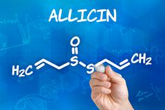 Hand with pen drawing the chemical formula of Allicin - stock photo