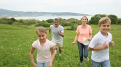 Family of four running in countryside Stock Footage