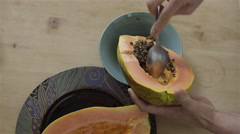 Scooping out the seeds from a Papaya. 4K UHD. Stock Footage