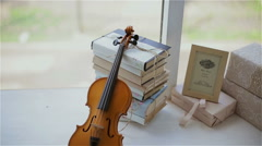 beautiful decor in the studio, violin and books on the window - stock footage