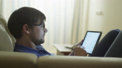 Man is Laying on Couch and Typing a Message on Tablet at Home Stock Footage