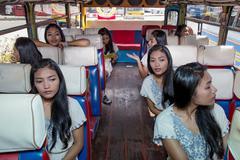 Many identical passenger clones sitting inside older bus Stock Photos