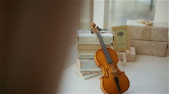Beautiful decor in the studio, violin and books on the window Stock Footage