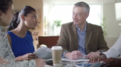 4k Multi-ethnic business group discuss figures in a business meeting  - stock footage
