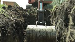 Excavator digging channel, shovel close up, low angle view. Stock Footage