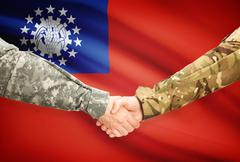 Soldiers shaking hands with flag on background - Burma - stock illustration
