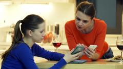 Two beautiful girlfriends talking over smartphone in the kitchen at home HD Stock Footage
