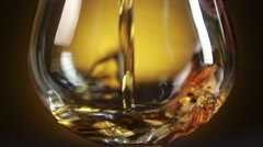 Stock Video Footage of Cognac pouring from bottle into glass with splash on yellow background. Close up